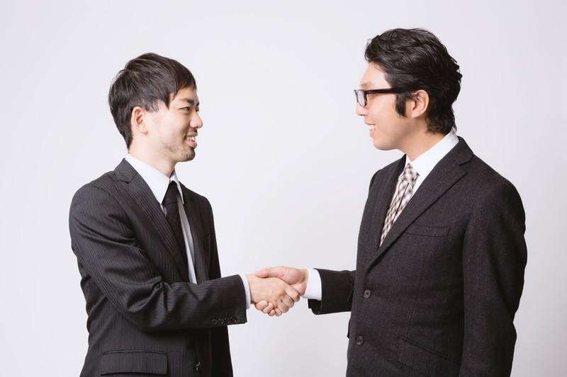 交渉成立して握手をするサラリーマン