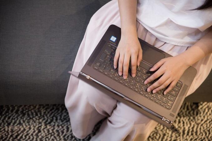 膝の上でノートパソコンを操作する女性
